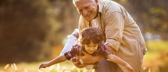 Opa spielt draußen mit dem Enkelkind